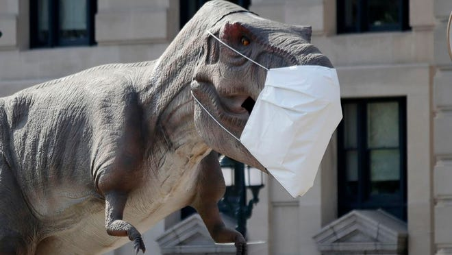 A dinosaur replica wears a mask outside Union Station in Kansas City, Mo., Wednesday, Aug. 5, 2020. The dinosaur is promoting a Dinosaur Road Trip exhibit.