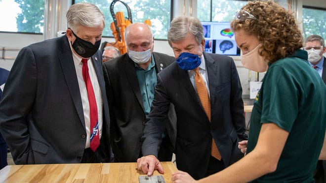 From left- Missouri Gov. Mike Parson, Rep. Don Mayhew and Sen. Roy Blunt examine a laser-printed sample from S&T student Michelle Gegel's machine.