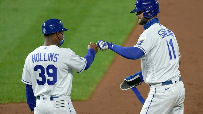 Kansas City Royals' Bubba Starling (11) celebrates with first base coach Damon Hollins (39) after hitting an RBI-single during the eighth inning of a baseball game against the Cleveland Indians, Monday, Aug. 31, 2020, in Kansas City, Mo.