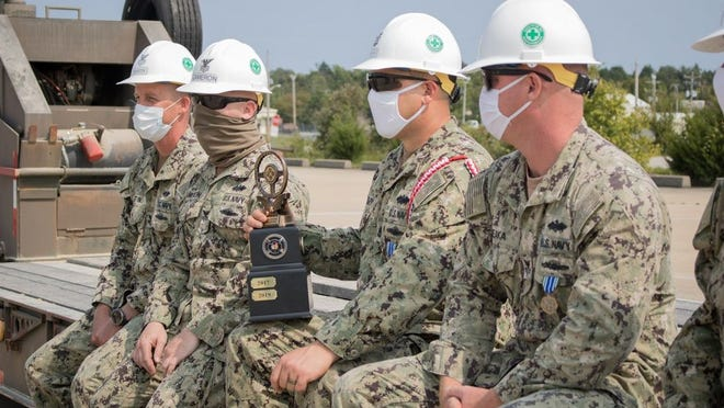 Sailors assigned to the Center for Seabees and Facilities Engineering Detachment Fort Leonard Wood sit with their trophy after finishing first in the Joint Truck Rodeo Friday.