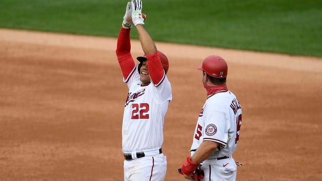 Washington Nationals' Juan Soto (22) reacts at first after his single during the second inning of a baseball game against the New York Mets, Sunday, Sept. 27, 2020, in Washington. Also seen is Nationals first base coach Bob Henley at right. The Nationals won 15-5.