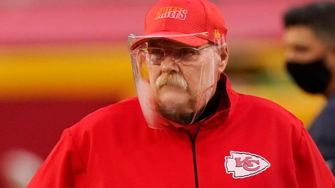 Kansas City Chiefs head coach Andy Reid wears a face shield as he watches players warm up before an NFL football game against the Houston Texans Thursday, Sept. 10, 2020, in Kansas City, Mo.