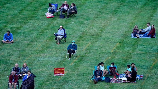 People are socially distanced as they listen to music of the Kansas City Symphony on the lawn at the Liberty Memorial Saturday, Sept. 19, 2020, in Kansas City, Mo.