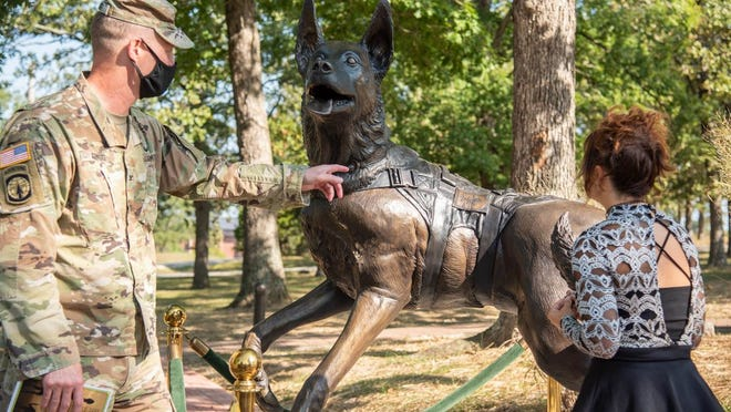 Col. Matthew Gragg, USAMPS director of training, and Victoria Carriger admire the details on the 5-foot tall bronze statue honoring Military Working Dogs. The statue was dedicated Monday following the annual Memorial Tribute as part of the Military Police Regimental Week.