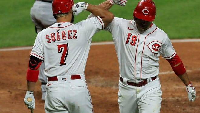 Cincinnati Reds' Eugenio Suarez, left, congratulates Joey Votto, who hit a solo home run during the third inning of the team's baseball game against the Chicago White Sox in Cincinnati, Friday, Sept. 18, 2020.