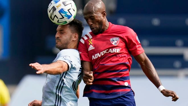 Sporting Kansas City defender Luis Martins, left, heads the ball against FC Dallas forward Fafa Picault, right, during the first half of an MLS soccer match in Kansas City, Kan., Saturday, Sept. 19, 2020.