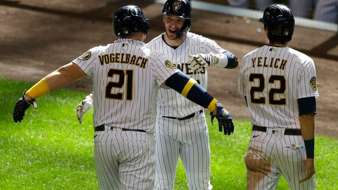 Milwaukee Brewers' Daniel Vogelbach, left, is congratulated by Ryan Braun, center, and Christian Yelich, right, after hitting a three-run home run during the sixth inning of a baseball game against the Kansas City Royals Sunday, Sept. 20, 2020, in Milwaukee.