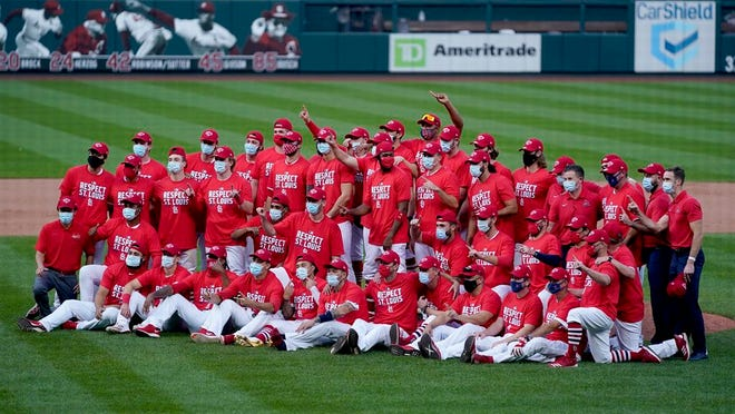 Members of the St. Louis Cardinals celebrate after defeating the Milwaukee Brewers in a baseball game to earn a playoff birth Sunday, Sept. 27, 2020, in St. Louis.