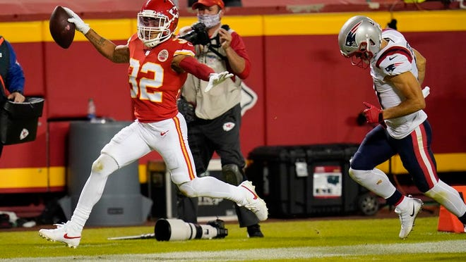Kansas City Chiefs safety Tyrann Mathieu (32) runs from New England Patriots wide receiver Julian Edelman, right, while returning an interception 25-yards for a touchdown during the second half of an NFL football game, Monday, Oct. 5, 2020, in Kansas City.