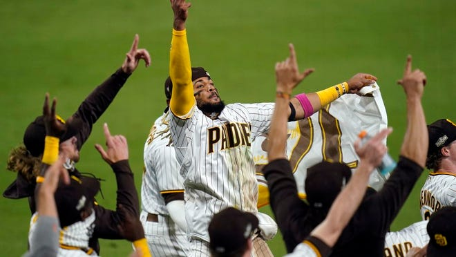 San Diego Padres' Fernando Tatis Jr., center, celebrates with teammates after the Padres defeated the St. Louis Cardinals 4-0 in Game 3 of a National League wild-card baseball series Friday, Oct. 2, 2020, in San Diego. The Padres won the series and advanced to the Division Series.
