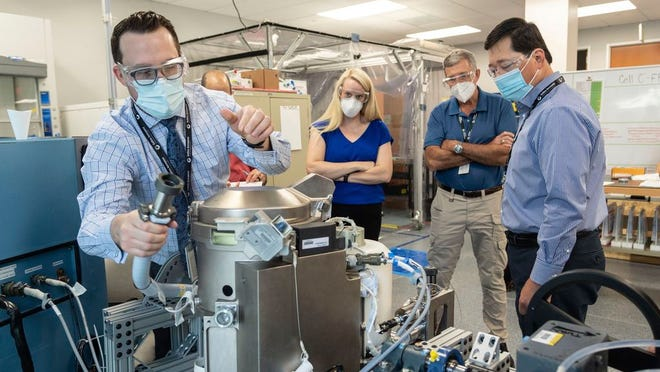 In this June 18, 2020 photo provided by NASA, astronaut Kate Rubins, center, and support personnel review the Universal Waste Management System, a low-gravity space toilet, in Houston. The new device is scheduled to be delivered to the International Space Station on Oct. 1, 2020.