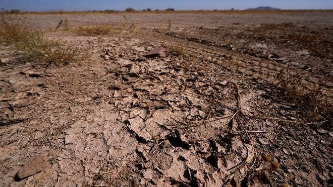 FILE - In this Wednesday, Sept. 30, 2020 file photo, dry desert soil cracks due to the lack of monsoon rainfall in Maricopa, Ariz. In a report released on Thursday, Oct. 15, 2020, National Oceanic and Atmospheric Administration forecasters see a dry winter for all of the south from coast-to-coast and say that could worsen an already bad drought.