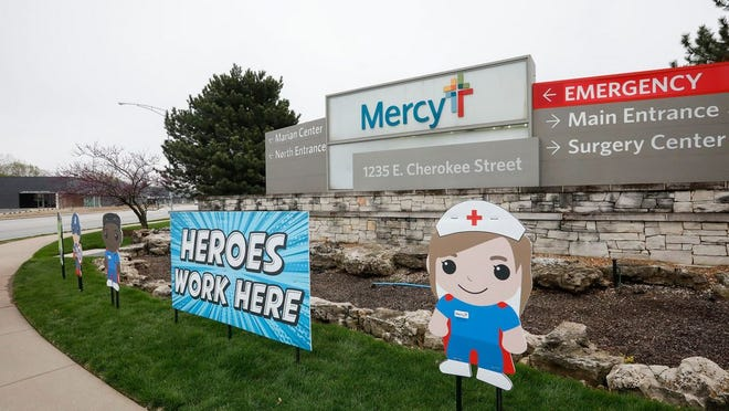"""A sign outside of Mercy Hospital reads, """"Heroes Work Here"""" as a show of support to healthcare workers during the novel coronavirus pandemic."""
