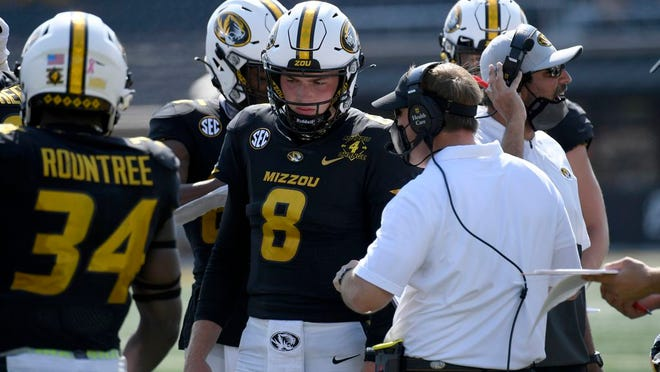 Missouri head coach Eliah Drinkwitz talks with quarterback Connor Bazelak (8) during the second half of an NCAA college football game against LSU Saturday, Oct. 10, 2020, in Columbia, Mo.
