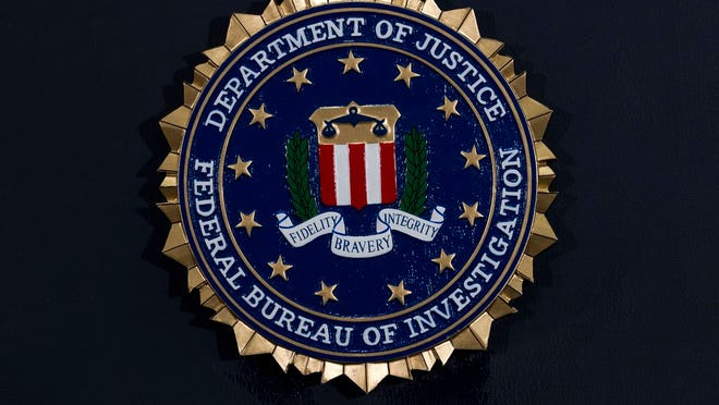 FILE - This Thursday, June 14, 2018, file photo, shows the FBI seal at a news conference at FBI headquarters in Washington. In an alert Wednesday, Oct. 28, 2020, the FBI and other federal agencies warned that cybercriminals are unleashing a wave of data-scrambling extortion attempts against the U.S. healthcare system that could lock up their information systems just as nationwide cases of COVID-19 are spiking.