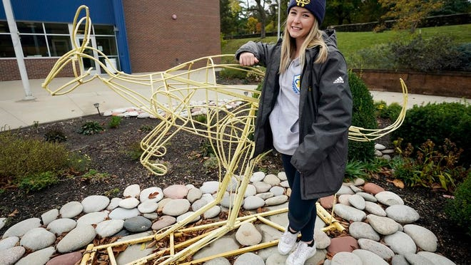 """Madison Zurmuehlen stands next to a sculpture of the University of Missouri-Kansas City's mascot outside the soccer facility in Kansas City, Mo., Friday, Oct. 23, 2020. Amid pandemic restrictions aimed at keeping students safe and healthy, colleges are scrambling to help them adjust. Zurmuehlen said daily practices, with masks, are """"the one thing I look forward to,"""" so it was tough when campus sports were canceled for two weeks after an outbreak among student athletes and staff."""