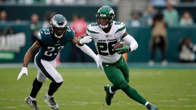 This Oct. 6, 2019, file photo shows New York Jets' Le'Veon Bell, right, rushing past Philadelphia Eagles' Rodney McLeod during the first half of an NFL football game in Philadelphia.