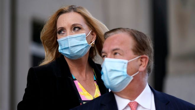 FILE - In this Oct. 14, 2020 file photo, Mark and Patricia McCloskey leave following a court hearing in St. Louis.