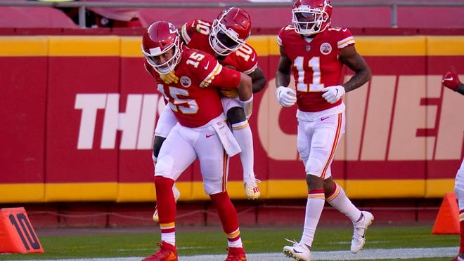 Kansas City Chiefs quarterback Patrick Mahomes (15) gives wide receiver Tyreek Hill (10) a ride on his back to the bench as wide receiver Demarcus Robinson (11) looks on following Hill's touchdown catch in the second half of an NFL football game against the New York Jets on Sunday, Nov. 1, 2020, in Kansas City, Mo.