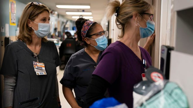 In this Nov. 19, 2020, file photo, registered Nurse Kristina Shannon, from left, chaplain Andrea Cammarota, and Emergency Room charge nurse Cathy Carter watch as medical workers try to resuscitate a patient who tested positive for coronavirus in the emergency room at Providence Holy Cross Medical Center in the Mission Hills section of Los Angeles.