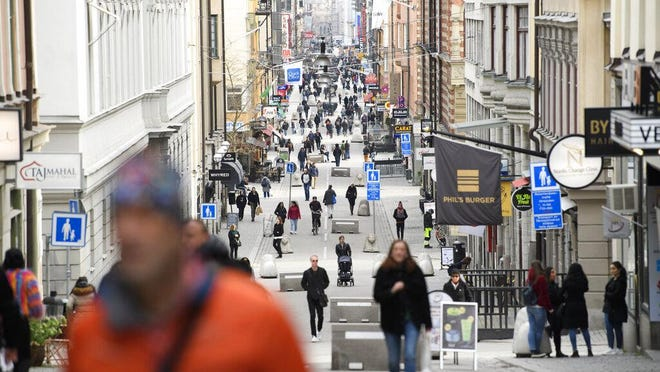People go about their daily routine on Drottninggatan, the main shopping street in Stockholm, Sweden, amid the new coronavirus pandemic in March.