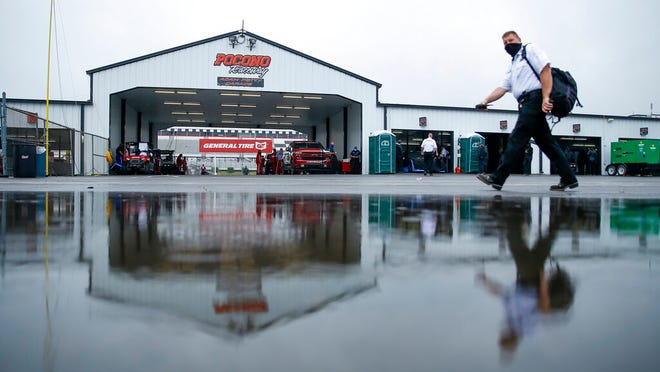 A man is reflected in a rain puddle as he walks near the Cup cars garages before the scheduled NASCAR Truck Series auto race at Pocono Raceway, Saturday, June 27, 2020, in Long Pond, Pa.