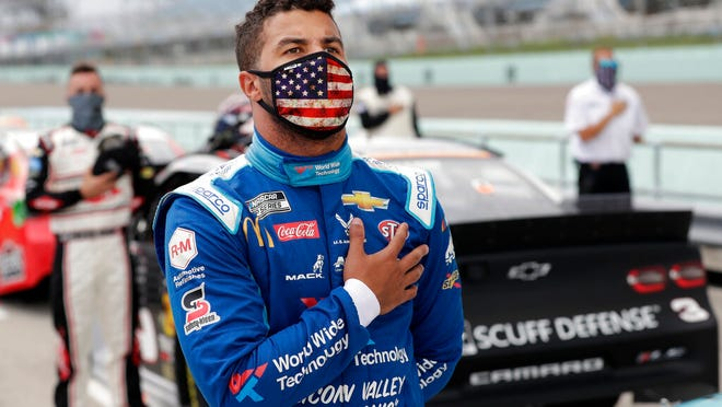 Bubba Wallace stands for the national anthem before a NASCAR Cup Series auto race Sunday, June 14, 2020, in Homestead, Fla.