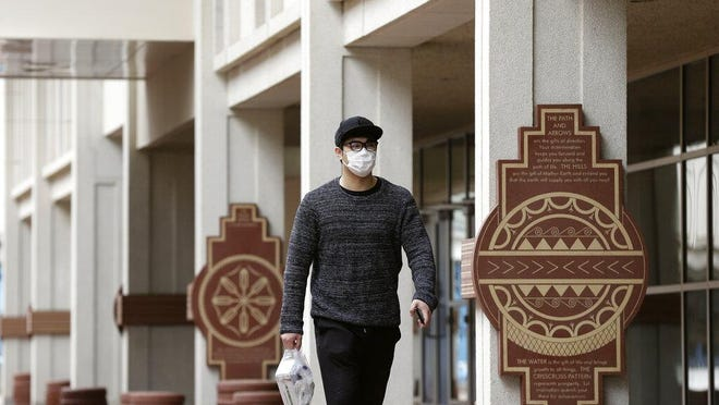 A pedestrian walks through campus at the University of North Carolina in Chapel Hill March 18.