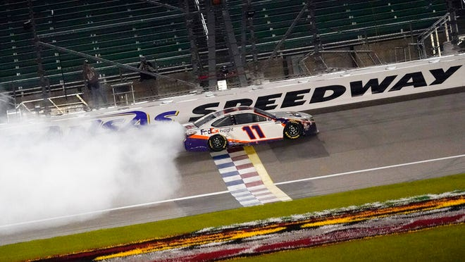 Denny Hamlin does a burnout after winning a NASCAR Cup Series auto race at Kansas Speedway in Kansas City, Kan., Thursday, July 23, 2020.