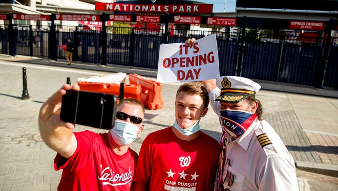 "From left, Rob Johnston of Alexandria, Va., and his son Robbie, 15, take a photo with Ted Peters of Haymarket, Va., who calls himself ""Captain Obvious"" outside Nationals Park before the New York Yankees and the Washington Nationals play an opening day baseball game, Thursday, July 23, 2020, in Washington."