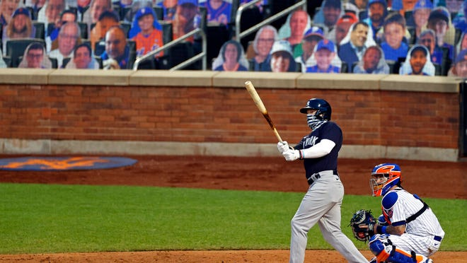 New York Yankees' Clint Frazier, left, watches his two-run home run against the New York Mets during the fourth inning of a baseball spring training game Saturday, July 18, 2020, in New York.