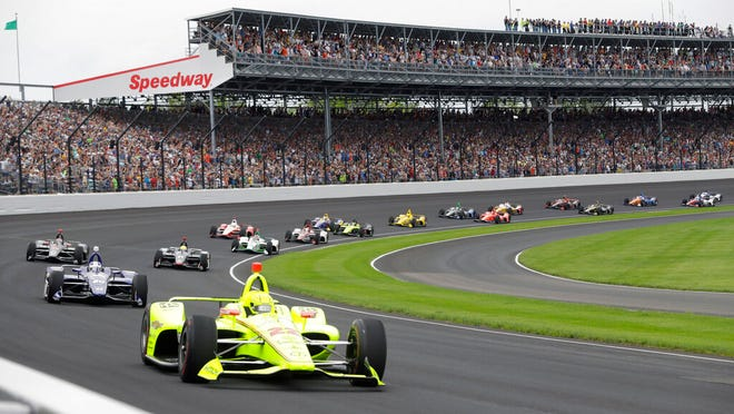 """FILE - In this May 26, 2019, file photo, Simon Pagenaud, of France, leads the field through the first turn on the start of the Indianapolis 500 IndyCar auto race at Indianapolis Motor Speedway in Indianapolis. Roger Penske has reversed course and decided not to allow fans at the Indianapolis 500 later this month. The 104th running of """"The Great American Race†will be the first without spectators, who showed up at Indianapolis Motor Speedway every year, even during the Great Depression."""