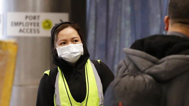 A airport agent, who declined to be identified, wears a protective mask as she waits to assist international travelers at SeaTac International Airport, Monday, Feb. 24, 2020, in SeaTac, Wash. Few travelers or workers were taking such precautions at the airport Monday, but a new virus is taking aim at a broadening swath of the globe, with officials in Europe and the Middle East now scrambling to limit it. The number of people sickened by the coronavirus topped 79,000 globally, and wherever it sprung up, officials rushed to try to contain it.