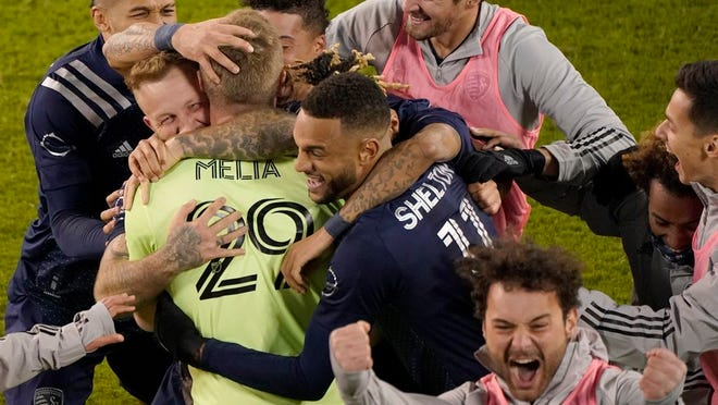 Sporting Kansas City players celebrate after winning an MLS soccer match against the San Jose Earthquakes with a penalty kick in overtime Sunday, Nov. 22, 2020, in Kansas City, Kan.