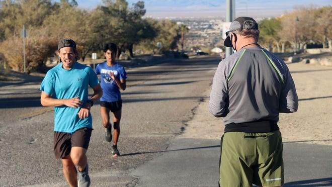 Burroughs High School cross country head coach Anthony Barnes and a limited number of athletes practice behind Cerro Coso Community College on Monday afternoon. CIF announced a postponement of full practices and competition on Tuesday afternoon.