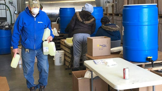 In this Thursday April, 9, 2020 photo, employees at a new hand sanitizer factory work to load and manufacture product at the facility in Bismarck, N.D. A number of North Dakota businesses have switched gears amid the coronavirus outbreak to make products in short supply.