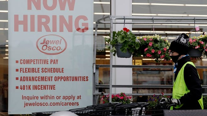 A man pushes carts as a hiring sign shows at a Jewel Osco grocery store in Deerfield, Ill., Thursday, April 23, 2020. Friday, Dec. 4, monthly U.S. jobs report will help answer a key question hanging over the economy: Just how much damage is being caused by the resurgent coronavirus, the resulting restrictions on businesses and the reluctance of consumers to shop, travel and dine out?