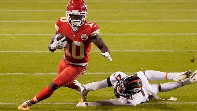 Kansas City Chiefs wide receiver Tyreek Hill (10) avoids Denver Broncos cornerback A.J. Bouye (21) in the first half of an NFL football game in Kansas City, Mo., Sunday, Dec. 6, 2020.