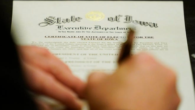 A member of Iowa's Electoral College signs the Certificate of Vote of Electors for the State of Iowa, Monday, Dec. 14, 2020, at the Statehouse in Des Moines, Iowa.