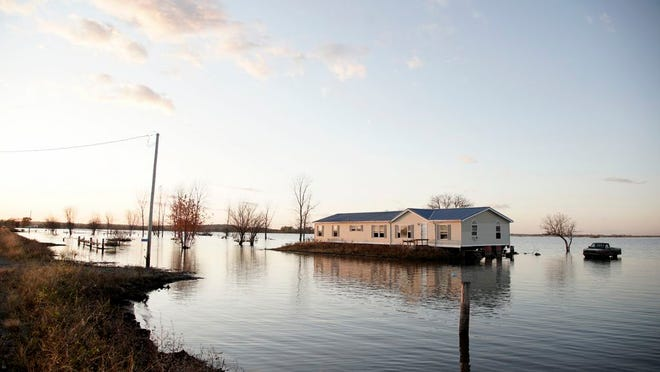 FILE - In this Oct. 22, 2019 file photo, a home is surrounded by Missouri River floodwaters in Bartlett, Iowa. A judge has ruled that the federal government must pay landowners on the lower Missouri River for flooding damage caused by the Army Corps of Engineers' efforts to protect endangered species. Judge Nancy Firestone, with the U.S. Court of Federal Claims, ruled this week that the Corps caused increased flooding by changing habitat on the river to comply with the Endangered Species Act.