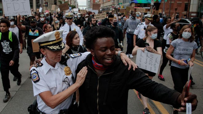 Columbus Division of Police Deputy Chief Jennifer Knight marches with 21-year-old protester Earl Jones.