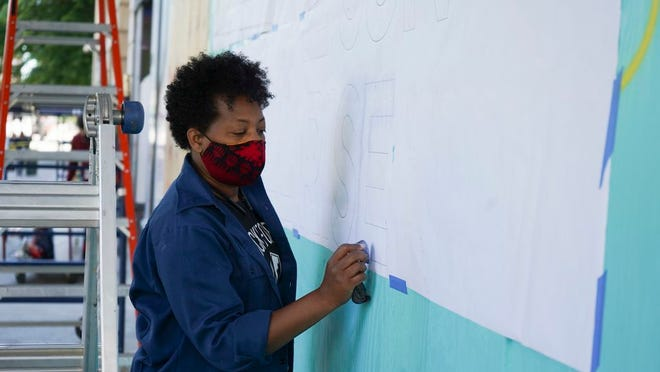 Lisa McLymont works on a mural outside the Ohio Theatre in early June.