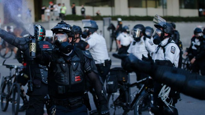 Columbus police officers use pepper spray Friday to disperse protesters near City Hall during nationwide protests following the death of George Floyd. Their riot gear has no badges or body cameras. The tape seen on their chests is for unit identification.