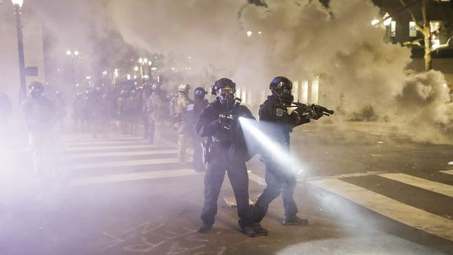Federal officers deploy tear gas and crowd control munitions at demonstrators during a Black Lives Matter protest at the Mark O. Hatfield United States Courthouse Tuesday, July 28, 2020, in Portland, Ore.
