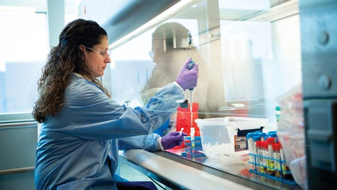 OSU employee Sandra VanVranken works with coronavirus test specimens in a new lab created as a collaboration between Ohio State University and Battelle.