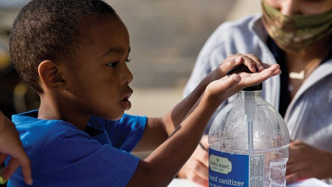 A student uses hand sanitizer during drop-off at Heavenly Kids Center for Learning in Downtown Columbus.