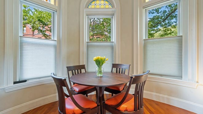 Colorful stained-glass transoms accent the bow windows in the dining area.