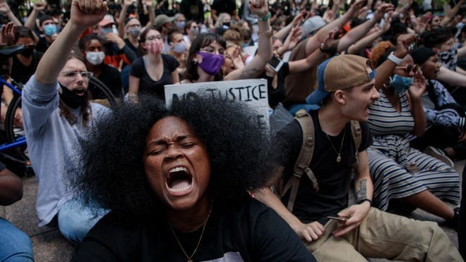 """Ebri Yahloe, 26, of Columbus, chants, """"No Justice, No Peace"""" while sitting along High Street on June 1."""