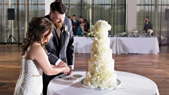 Katie and Sean Rowley cut into their cake, which featured live flowers and alternating tiers of buttercream and fondant icing.