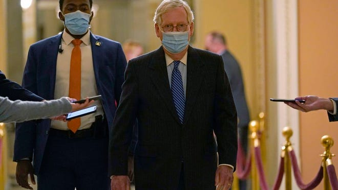 In this Dec. 15, 2029, photo, Senate Majority Leader Mitch McConnell of Ky., walks past reporters on Capitol Hill in Washington.